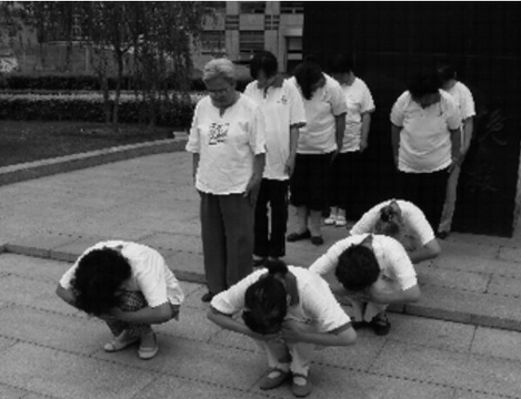 A simulation of roll call outside Beijing RTL Center. When your name is called, you must squat as illustrated. Otherwise, you must stand bowing down your head. Photo provided by Ye Jinghuan (野靖环).
