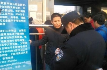 Xu Zhiyong outside a subway entrance/exit in February, 2013, calling parents to petition outside the Beijing municipal education commission.  He was being questioned by a police officer.