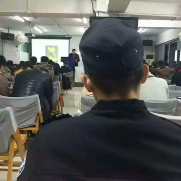 "A recent photograph taken at a gathering of the ""Blessing of Autumn Rain"" house church (秋雨之福) in Chengdu, showing the presence of a police officer monitoring the proceedings. The government is looking upon churches with increasing hostility, and its suppression of them seems likely only to deepen and expand."