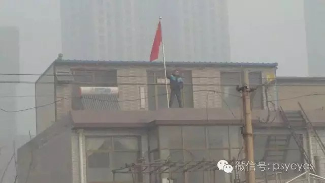 Jia Jinglong standing atop his home, trying to stop the demolition. Image Credit: China Change